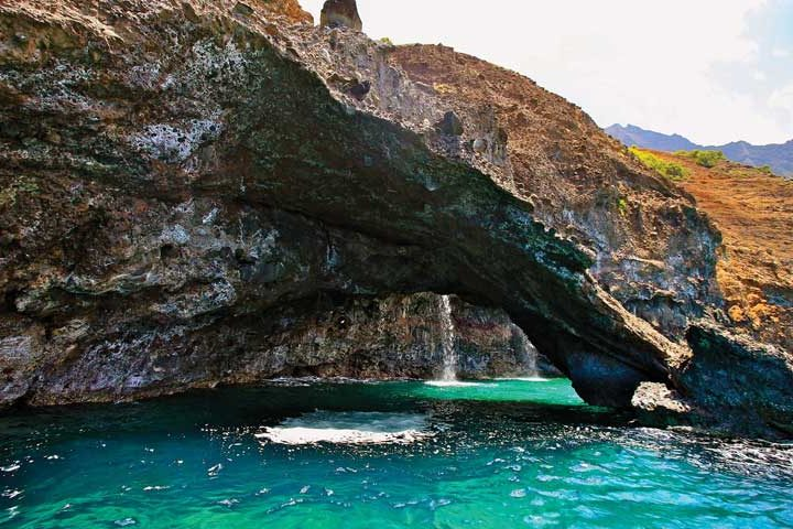 Spectacular sea arches have formed in the cliffs as a result of the pounding, Hawaiian surf.